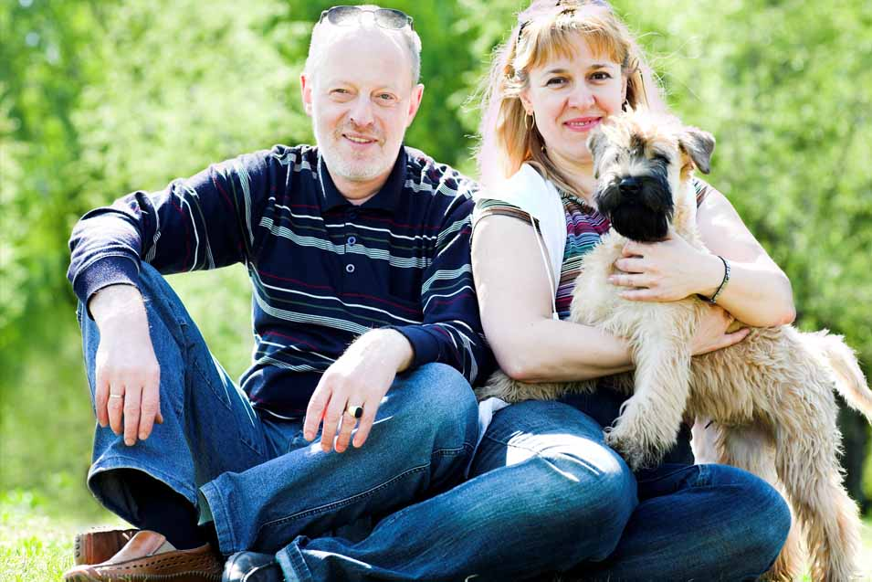 Picture of a Soft Coated Wheaten Terrier with man and woman