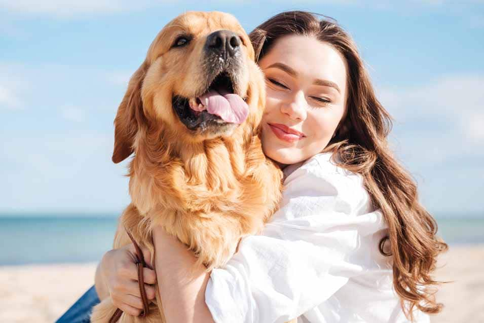 Picture of a woman hugging a Golden Retriever