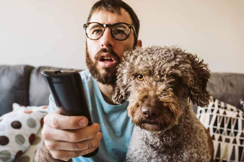 Picture of a man watching tv with his dog